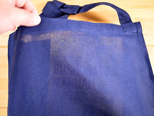 ネイビー色バッグの場合:中の本とバッグの生地がくっついた状態では本表紙の文字は見えませんが生地を浮かせて中に光をいれてやるとタイトル文字が読める透け感です
